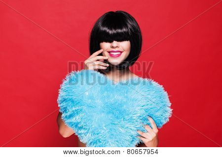 Pretty attractive smiling woman holding a blue plush heart. waiting for Valentine's Day. woman's lov