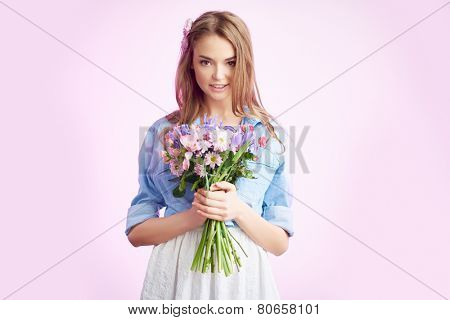 Young woman in casualwear holding flowers