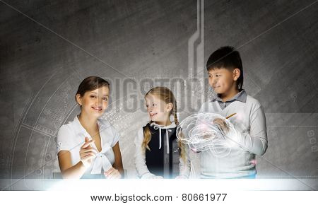 Young teacher and her pupils examining hologram of human brain