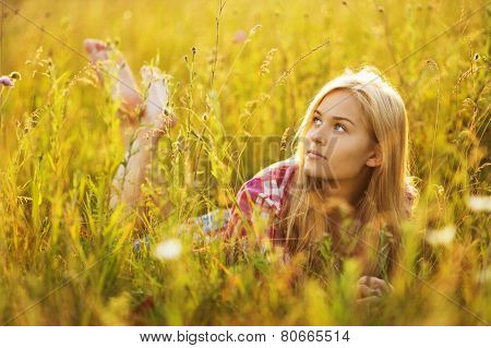 Beautiful Blonde Girl Lying In The Grass