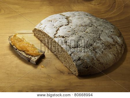Cut Loaf Of Fresh Baked Rye Bread With Orange Marmalade