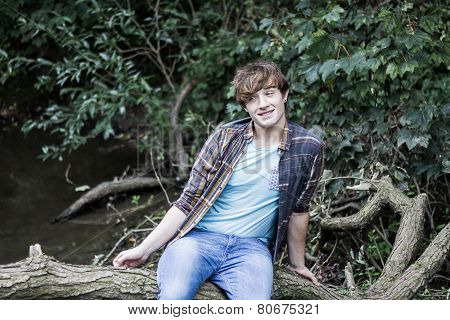young man sitting on branch over a stream