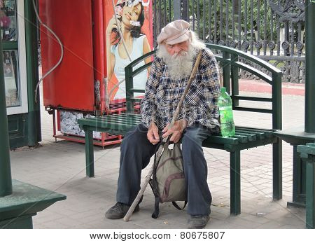 Senior Adult Man Sitting On The Bench Of A Bus Stop