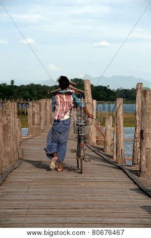 Villagers Bike Trailers On U-Bein Bridge,Myanmar.