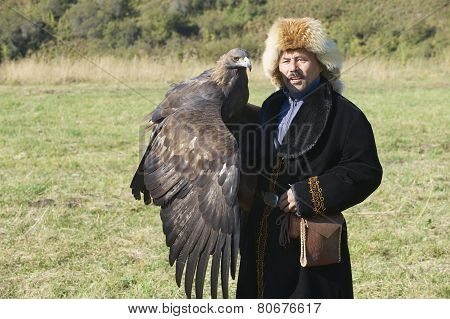Mongolian hunter holds golden eagle, circa Almaty, Kazakhstan.