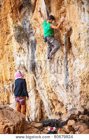 Man lead climbing on cliff, belayer watching hi