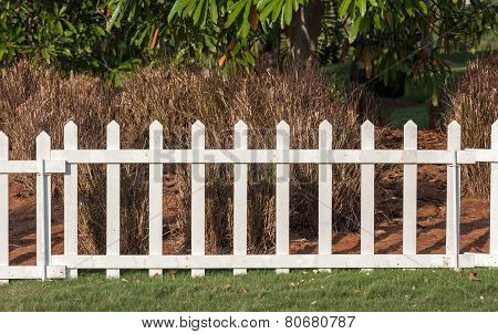 White Wooden Fence In Farmland Marks For Land Property And Dry Trees Background.