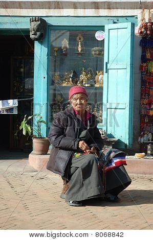 Anciana tibetana sentado cerca de Swayambhunath Stupa, Kathmandu, Nepal