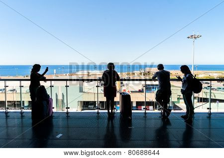 Silhouette Of Passengers Waiting On Open Terrace In Airport