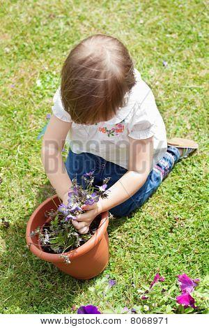 Sweet Girl Planting A Flower