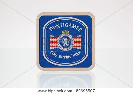 Beermat From Puntigamer Beer On A Glass Table.