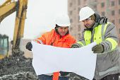 picture of engineering construction  - Civil engineers at construction site are inspecting ongoing works according to design drawings in difficult winter conditions - JPG