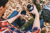 pic of thermos  - Hiker young man holding a cup of tea or coffee and thermos in autumn forest - JPG