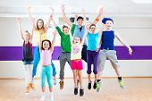 foto of health center  - Dance teacher giving children Zumba fitness class in gym - JPG