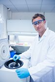 stock photo of centrifuge  - Smiling chemist using a centrifuge in lab - JPG