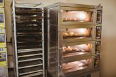 picture of bread rolls  - Bread rolls baking in oven in a commercial kitchen - JPG