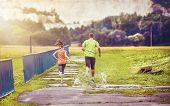 picture of rainy weather  - Young couple jogging on asphalt in rainy weather - JPG