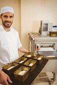 stock photo of tin man  - Happy baker holding tray of loaf tins in a commercial kitchen - JPG