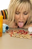 stock photo of tongue licking  - A woman with her tongue out getting ready to lick up her pills - JPG