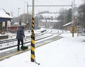 picture of snow shovel  - Woman with shovel clears snow from a platform on the station - JPG