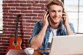 stock photo of nod  - Handsome young man in headphones working on laptop and smiling while acoustic guitar laying in the background - JPG