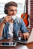 image of nod  - Handsome young man in headphones working on laptop and drinking coffee while acoustic guitar laying in the background - JPG