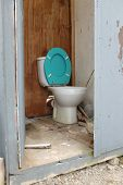 foto of cistern  - A door opens into a dirty wooden built toilet cubicle with a white bowl and blue lid. ** Note: Soft Focus at 100%, best at smaller sizes - JPG