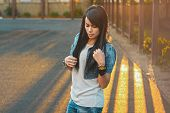 stock photo of swagger  - Beautiful girl in a denim jacket in the sunlight sunset.