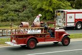 stock photo of mustering  - An antique fire department vehicle being driven in a fire muster parade - JPG