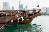 image of old boat  - Abu Dhabi buildings skyline with old fishing boats on the front - JPG