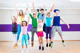 stock photo of teachers  - Dance teacher giving children Zumba fitness class in gym - JPG