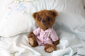 pic of pyjama  - Cute teddy bear in pink pyjama resting in the bed - JPG