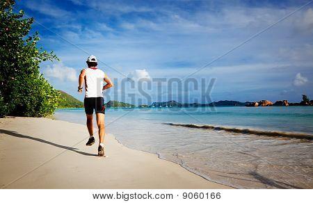 Mann läuft an einem tropischen Strand