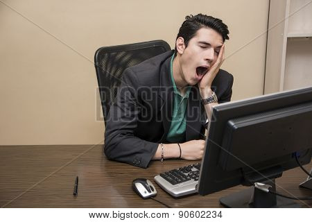 Tired bored young businessman sitting in office yawning