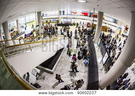 Tourists Wait For Their Baggage At The Airport