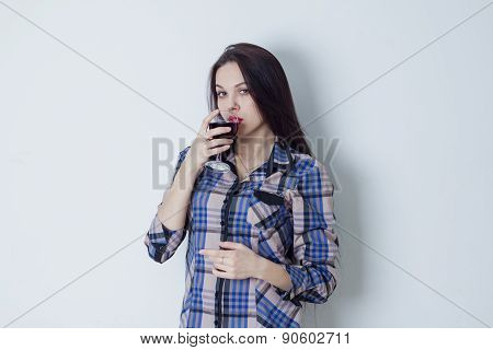 Young woman looking at camera and drinking red wine