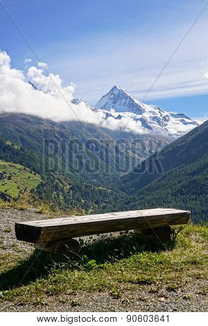 Rustic Wooden Bench Overlooking Swiss Alps.