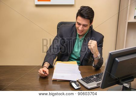 Happy successful young businessman, sitting at desk in office