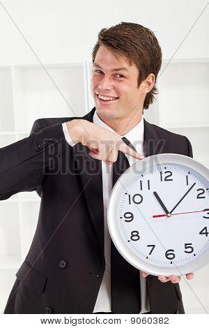 handsome businessman holding clock