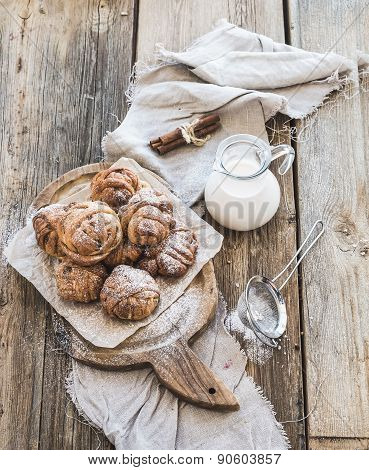Cinnamon buns with sugar powder on rustic wooden board, jug of milk,  dark grunge surface