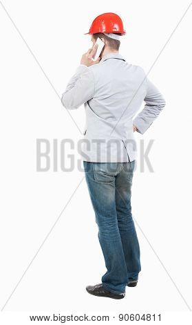 Backview of business man in construction helmet stands and enjoys tablet or using a mobile phone. Standing young guy.  Young businessman talks.