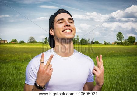 Young man at countryside, doing victory sign smiling