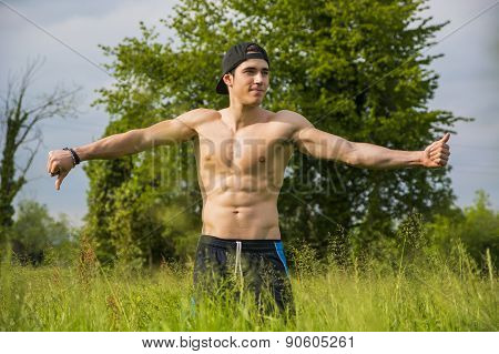 Shirtless young man doing funny pose standing