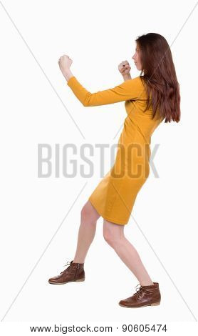 skinny woman funny fights waving his arms and legs. Rear view people collection.  backside view of person.  Isolated over white background. Girl dress in mustard in a fight.