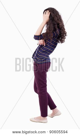 back view of standing young beautiful  woman.    Isolated over white background.girl in dress modest scratches his head in surprise. The woman in red jeans thoughtfully scratching his curly hair.