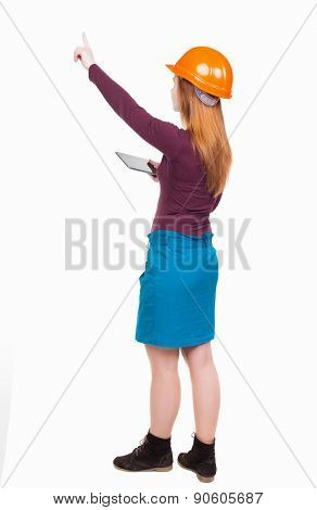 Backview of business woman in construction helmet with  tablet pc pointing. Standing young girl. Rear view people collection.  backside view of person. Engineer scorekeeper hand shows the work front.