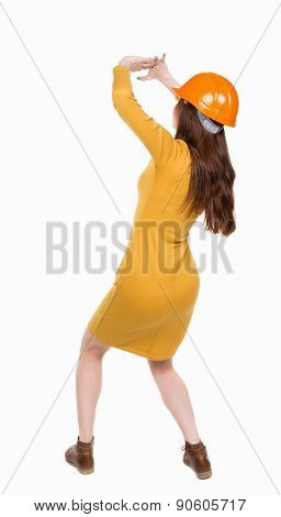 back view. woman in a dress and protective construction helmet protects hands from what is falling from above. Rear view people collection.  backside view of person.  Isolated over white background.