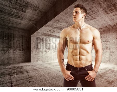 Muscular shirtless young man with jeans, indoors in empty warehouse.