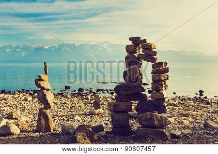 Stone figures on beach shore of Geneva lake in Switzerland, toned image