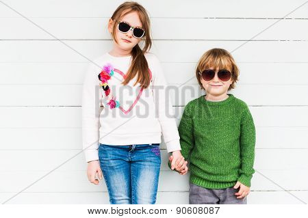 Fashion kids outdoors, wearing pullovers and sung lasses